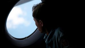 Mies katselee lentokoneen ikkunasta.