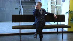 Petri Sirviö istuu penkillä ja puhuu puhelimeen.