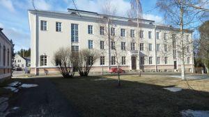 Kajaanin Seminaarin vanha päärakennus kylpee kevätauringossa.