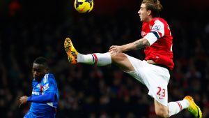Arsenalin Nicklas Bendtner (oik.) kurottaa korkeaan palloon. Hullin Maynor Figueroa (vas.) seuraa vierestä.