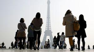Turistit kuvaavat savusumun peittämää Eiffel-tornia Pariisissa.