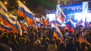 Ihmisiä aukiolla konserttilavan edustalla heiluttaen Venäjän lippuja.