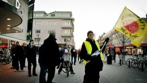"""Mielenosoittaja heiluttaa lippua, jossa lukee: """"Atomkraft? Nej tack."""""""