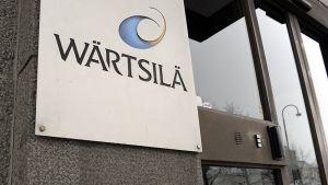 Wärtsilän nimilaatta konttorin oven viereisessä kiviseinässä.