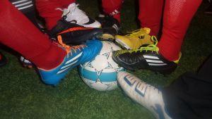 Kuvassa jalkapallojunioreita erilaiset nappulakengät jalassa pallon päällä.