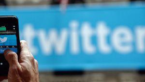 Mies kuvaa puhelimella Twitterin logoa