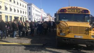 Ihmisiä jonottamassa amerikkalaisen koulubussin ympärillä.