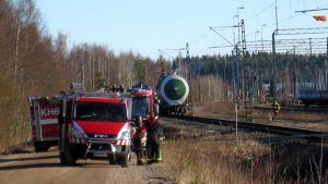 Paloautoja hitaasti savuavan säiliövaunun vieressä