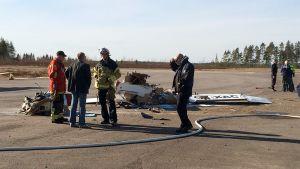 Pelastushenkilöstöä Nummelan lentokentällä pudonneen pienkoneen hylyn vierellä.