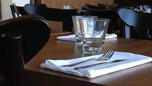 Aterimet ja lasit ravintolapöydässä.