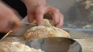 Kokki leikkaa leipää.