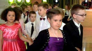 Lapset tanssivat Porvoon urheiluhallissa hienoissa vaatteissa.