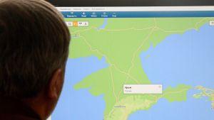 """21. maaliskuuta Moskovassa otetussa valokuvassa mies katsoo tietokoneen näytöltä karttaa, jossa lukee """"Krim, Venäjä""""."""