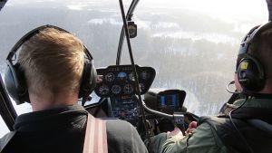Tervolan riistanhoitoyhdistyksen toiminnanohjaaja Kari Kokkonen ja lentäjä Keijo Korkiakoski tähystävät hirviä helikopterista.