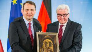 """Saksan ulkoministeri Frank-Walter Steinmeier (oikealla) esittelee Puolan ulkoministeri Radoslaw Sikorskin (vasemmalla) kanssa Francisco Guardin maalausta """"Palatsin portaat"""" Berliinissä 31. maaliskuuta 2014."""
