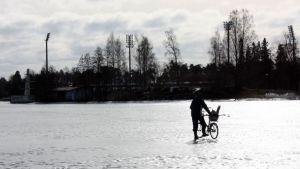 Mies järven jäällä polkupyörän kanssa