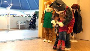 Miina- ja Manu-hahmot halivat kahta lasta kirjastossa