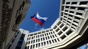 Venäjän lippu heiluu Krimin alueparlamentin rakennuksen edessä 18. maaliskuuta sinistä taivasta vasten.