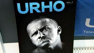 Urhotv:n mainosmateriaalia. Mustavalkoisessa valokuvassa mies katsoo tuimasti suu mutrulla kohti kuvaajaa. Ylhäällä sininen Urhotv:n logo.