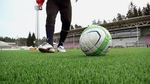Jalkapalloilija ja pallo stadionin nurmella.