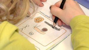 Lapsi piirtää esikoulukirjaan.