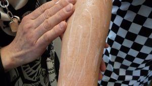 Naisen käsivartta rasvataan.