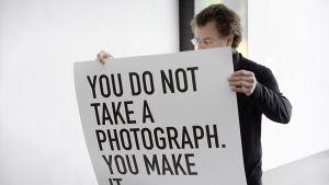 """Taiteilija, arkkitehti ja elokuvantekijä Alfredo Jaar Nykytaiteen museo Kiasmassa Helsingissä 8. huhtikuuta 2014. Hänellä on edessään teksti: """"You do not take a photograph. You make it."""""""
