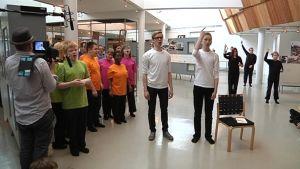 Onerva Mäen koulun oppilaat laulavat ja viittovat Rakennetaan koulu! -oopperassa.