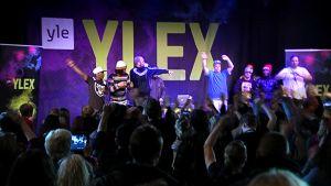 Useat suomalaiset räppärit esittävät rap-versioita J. Karjalaisen kappaleista Vaskivuoren lukiossa.