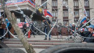 Venäjä-mielisiä mielenosoittajia barrikadilla ympäröidyn ja vallatun hallintorakennuksen edustalla.