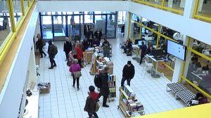 Ihmisiä yliopiston kirjaston aulassa.