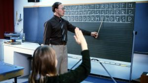 Arkistokuva: Opettaja opettaa liitutaulun edessä solmisointi-käsimerkkejä.
