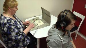 Kouluterveydenhoitaja Leena Puisto tekee kuulotestiä Jenni Niemiselle.