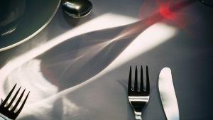 Ruokailuvälineitä ja viinilasin varjo pöydällä.