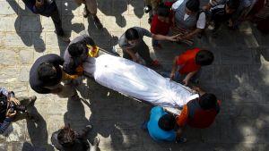 Ihmiset kantavat valkoiseen lakanaan peiteltyä ruumista.