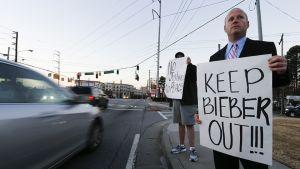 Kaksi miestä kadun varrella mielenosoitusplakaatien kanssa.