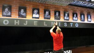 Lavastaja Kalle Nurminen kiinnittää ohjelmisto -tekstiä teatterilämpiön seinään
