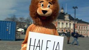 """Leijonapukuinen ihminen pitää kylttiä, jossa lukee """"haleja""""."""