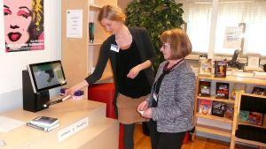 Kaksi naista testaa omatoimikirjaston lainaus- ja palautuspistettä