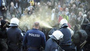 Poliisi käyttää kaasua mielenosoittajiin eduskuntalon portailla.