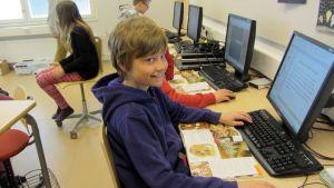 Kuvassa poika tietokoneella.