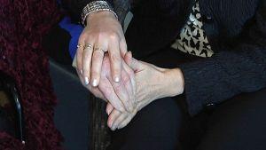 Nainen pitää vanhuksen kättä käsissään.