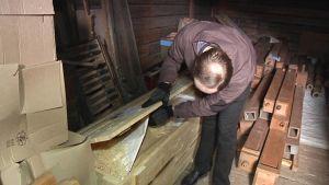 Mies raottaa laatikkoa ja tarkistaa vanhojen urkupillien kuntoa.