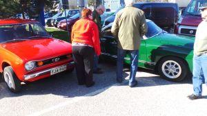 ihmiset katselevat vanhoja autoja