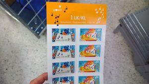 Kuvassa kannelta ja harmonikkaa esittävät postimerkit, jotka soittavat sovelluksen avulla Konsta Jylhän d-mollisottiisia.