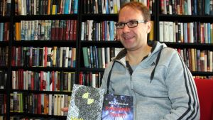 Kirjailija Mika Kähkönen pitää kädessään kahta kirjaansa.