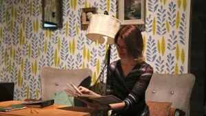 Nainen tutkii kirjaa.