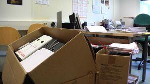 Kansioita pahvilaatikoissa toimistohuoneessa.