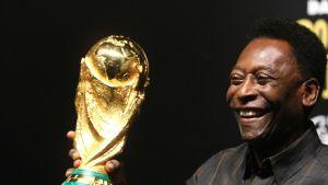 Brasilian legenda Pelé pitelee MM-kisojen pokaalia hymyillen kädessään.