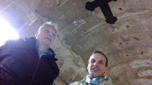 Kaksi miestä Uittotunnelin kattoon maalatun ristin alla